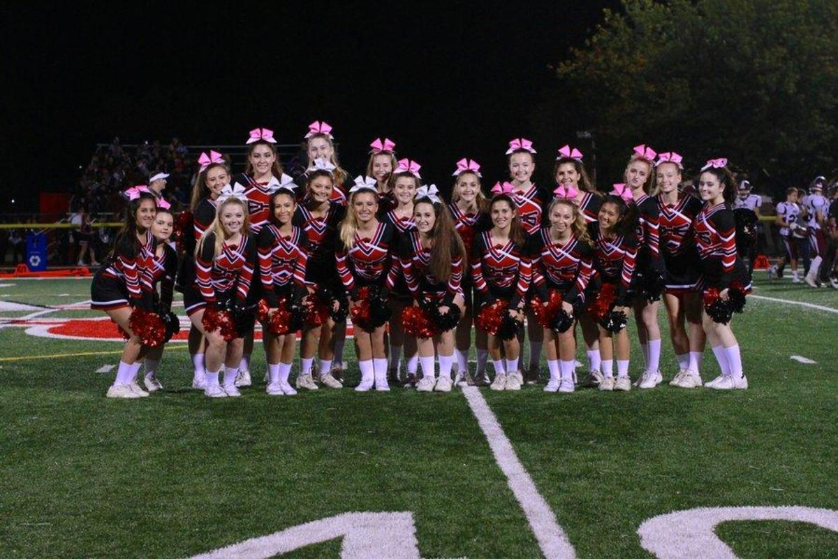 The varsity cheer team poses on the turf at Emerson's homecoming game on October 21, 2016. A handful of the team will soon begin the transition to competition cheer.