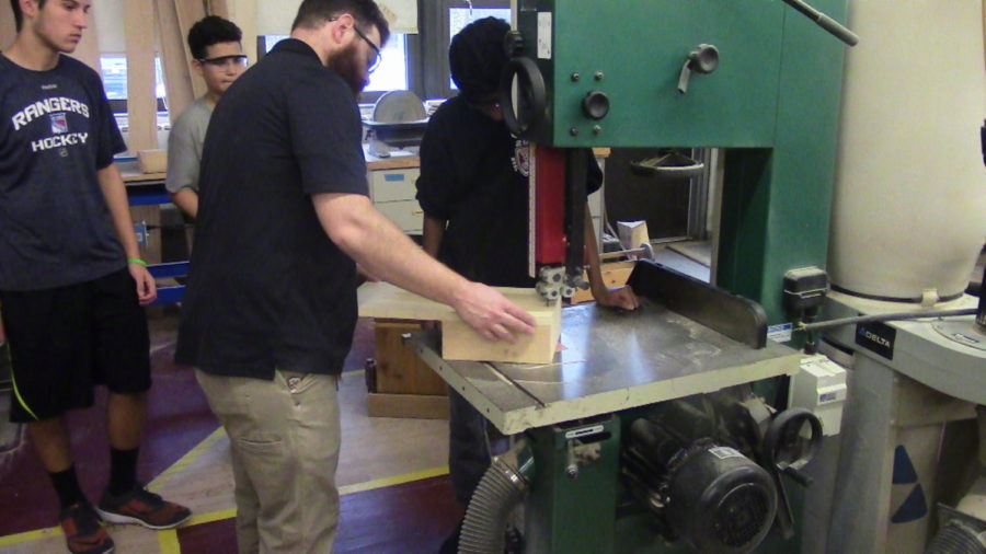 Mr.+Bliss+helps+a+student+use+the+Band+Saw.