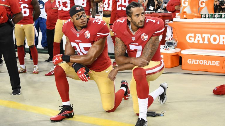 Colin+Kaepernick+%28right%29+kneeling+for+the+national+anthem+with+teammate+Eric+Reid+%28left%29+next+to+him.+