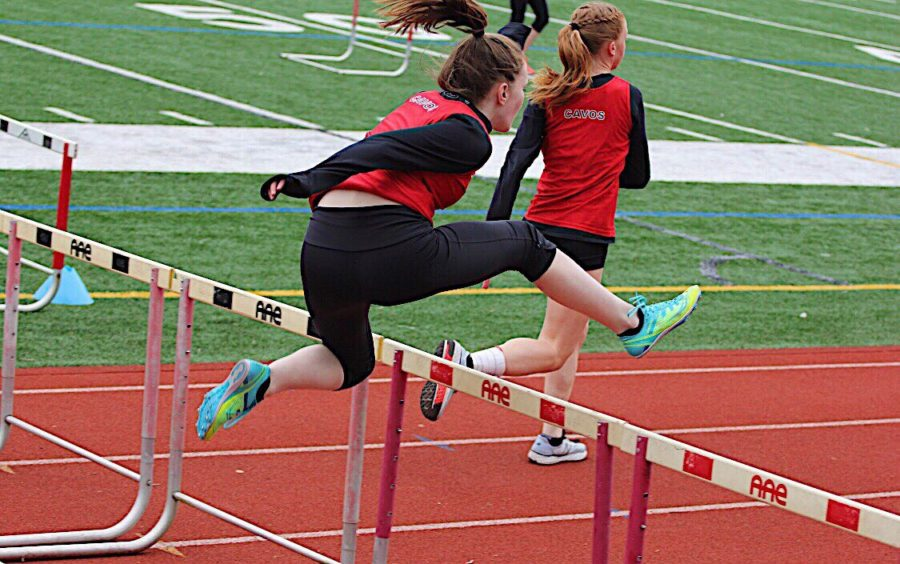 Sophomore+Emma+Callagy+jumps+over+the+hurdle+while+competing+in+an+event+at+a+track+meet.